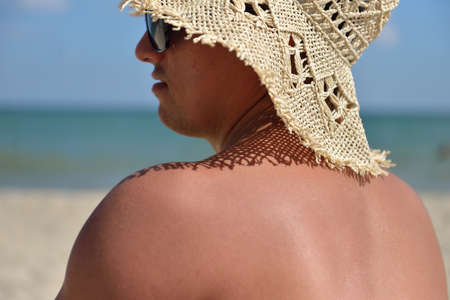 Funny picture of a relaxed young man with straw hat for woman and sunglasses look in the right side and stands to sunbath on the beach. Summer vacation. Sea in the background Stock Photo