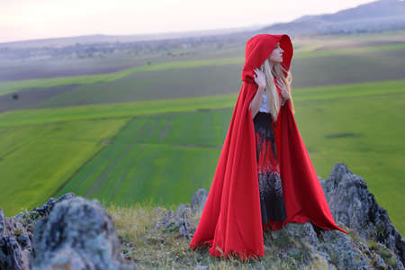 Beautiful blonde woman with red cloak standing barefoot in the wind on the edge of a mountain in the sunset light. Loneliness. Silence. Soothing landscape Stock Photo