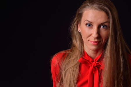 Beautiful blonde young woman in a red shirt posing in a studio on a black background photo
