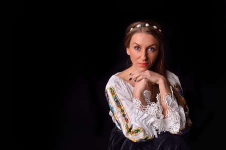 Closeup of a young Romanian woman with wreath of flowers on head dressed in traditional costume. Romanian folklore. Posing in a studio on a black background photo