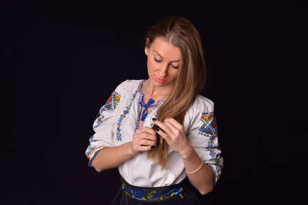 Closeup of a young Romanian woman dressed in traditional costume, playing with her hair. Romanian folklore. Posing in a studio on a black background photo