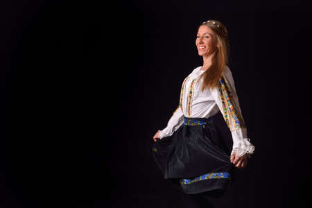 Closeup of a young Romanian woman dressed in traditional costume, holding his skirt on her hands and spins, playing. Romanian folklore. Posing in a studio on a black background Stock Photo
