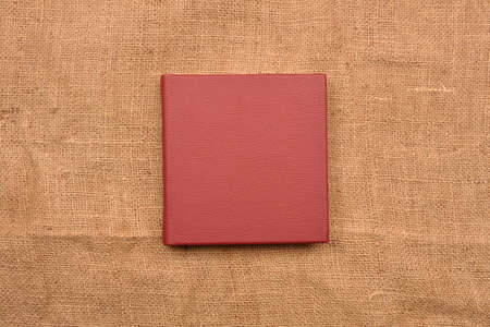 Picture of red leather photo album cover on jute background. Keeping memories alive throughout the years