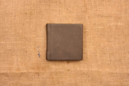 Picture of dark brown leather photo album cover on jute background. Keeping memories alive throughout the years