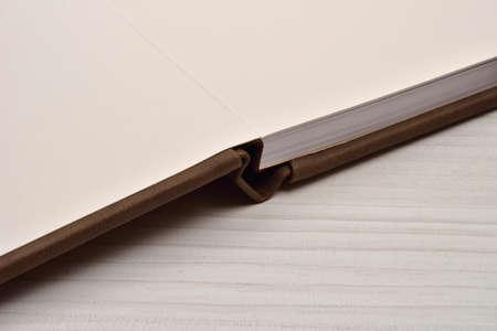 Close up of open brown leather photo album on white wooden background. Details of the front page Stock Photo