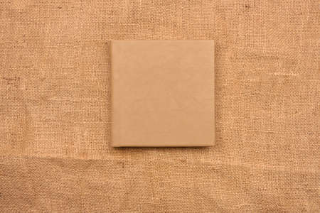 Picture of beige leather photo album cover on jute background. Keeping memories alive throughout the years Stockfoto