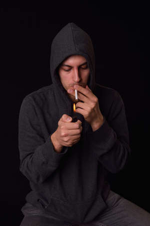 Teenager in a hooded sweatshirt lights a cigarette with lighter on a dark background. Harmful smoking concept. Unhealthy habits. Many others photos like this in my portofolio