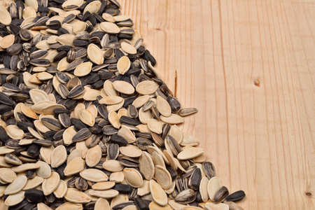Macro image of different sunflower and pumpkin seeds on wooden background. Health. Selective focus