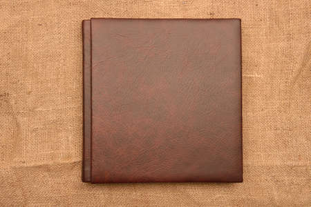 Picture of brown leather photo album cover on jute background. Keeping memories alive throughout the years Stockfoto