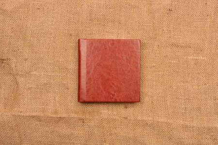 Picture of reddish brown leather photo album cover on jute background. Keeping memories alive throughout the years