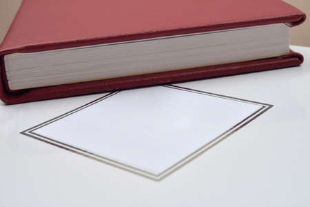 Side of christening red leather photo album and white storage box with space for text. Details. Copy space