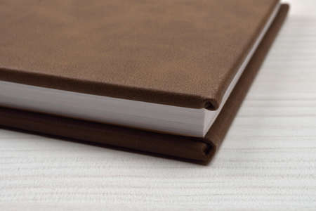 Close up of side brown leather photo album on white wooden background, details. Keeping memories alive throughout the years