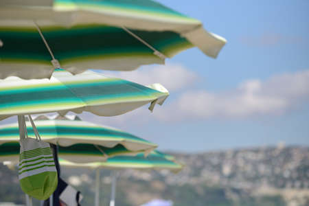 Detail of colorful umbrellas on the beach on a sunny summer day. Symbolic photo for holidays, mass tourism, sunburn
