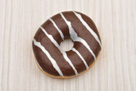 Chocolate donut with stripes on white wooden table. Sweets. Selective focus Stock Photo