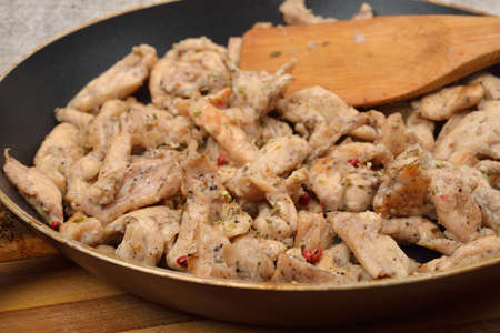 Chicken breast fillet cooked with different kinds of ingredients put in a pan with a wooden spoon. Close view Stockfoto