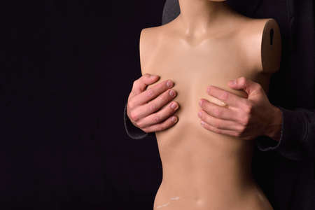 Serious man dressed in black hoodie holding in his arms a plastic women body mannequin on dark background. Loneliness