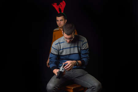 Young man standing on a chair and looking an old camera, behind him is a young man wearing reindeer horns with funny expression on dark background