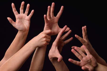 Many desperate female and male hands elevated into the air trying to reach or grab something on a black background Stockfoto