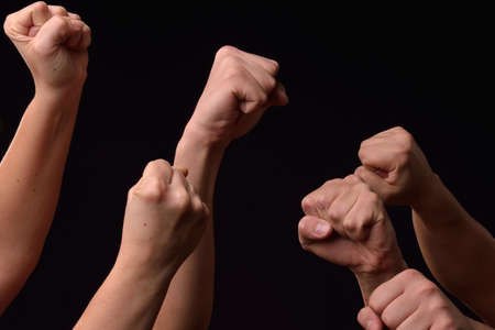 Group of female and male hands showing fists raised up on black background. Team. Power. Leader. Revolt Stock Photo