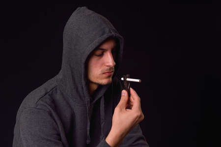 Teenager in black hooded sweatshirt holds with a clothes hanger a cigarette and looks at it on a dark background. Harmful smoking. Unhealthy habits.