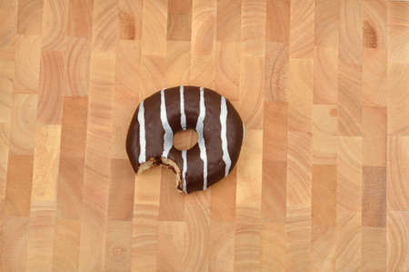 Bite chocolate donut with stripes on wooden background. Sweets. Selective focus. Copy space