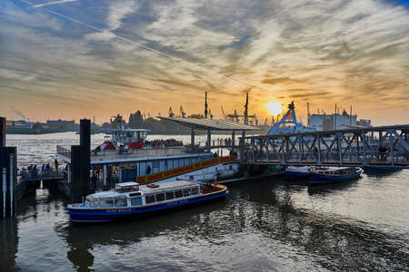 embark: HAMBURG GERMANY - NOVEMBER 01 2015: Tourists embark for the last harbor tour at the famous gangways of the harbor of Hamburg and enjoy a scenic sundown.