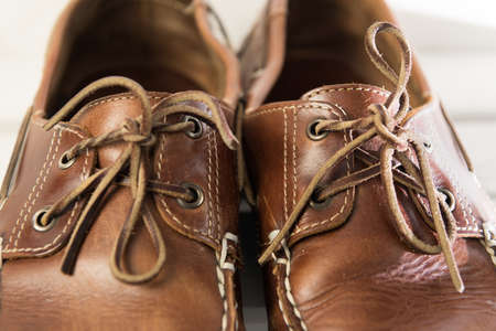 Pair of worn out brown casual leather shoes in front of white wooden background Stock Photo