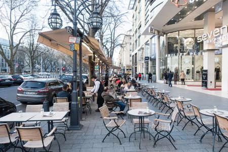 DUESSELDORF, DUITSLAND - 12 maart 2017: Onbekende shoppers wandelen langs de Koenigsallee en passeren een schilderachtig café met onbekende personen.