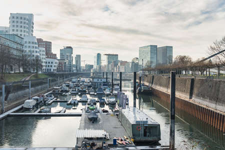 DUESSELDORF, GERMANY - JANUARY 20, 2017: The marina on the other side of the New Media Harbor hosts private and commercial vessels. Editorial