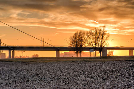 DUESSELDORF, GERMANY - JANUARY 20, 2017: The winter sun goes down over a large bridge and bathes everything in orange warm light.