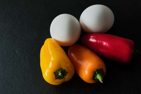 light slate gray: Low Carb - Two white eggs with three colorful mini paprikas on a dark slate background.