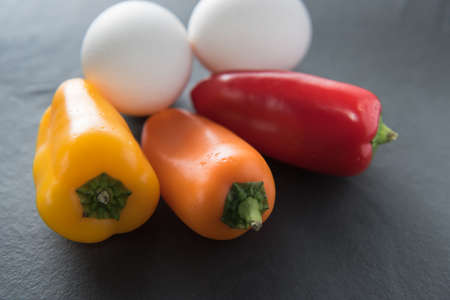 light slate gray: Low Carb - Two white eggs with three colorful mini paprikas on a dark slate background - vivid light.