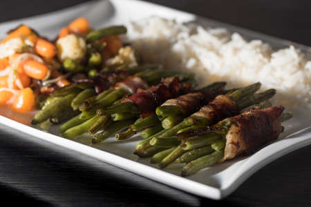 light slate gray: Low Carb - Green beans wrapped in bacon woth mixed vegetables and rice on white plate,