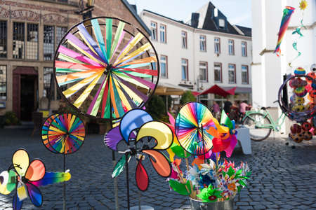 dom: XANTEN, GERMANY - SEPTEMBER 07, 2016: Colorful whirligigs contrasting with the background of a shopping street