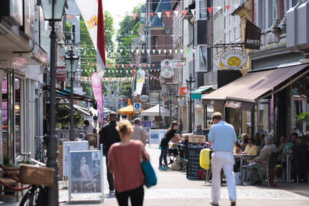 NEUSS, GERMANY - AUGUST 08, 2016: Pedestrants walking along a city shopping street with bars
