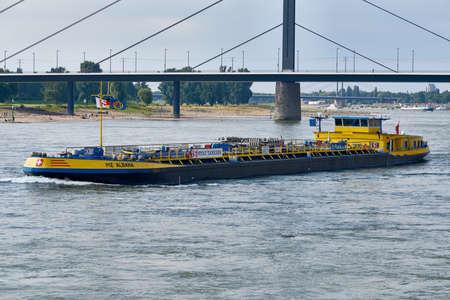 DUESSELDORF, DUITSLAND - AUGUSTUS 06, 2016: Een gastankschip drijft de rivier Rijn stroomopwaarts terwijl de visotors langs de stranden op de overkant van de Rijn wandelen.