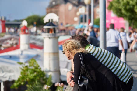 DUESSELDORF, GERMANY - AUGUST 06, 2016: An unidentified couple leans on the wall of the upper part of the Rhine promenade and looks around at all the other people and attractions.