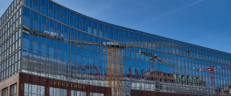 HAMBURG, GERMANY - MARCH 26, 2016: The new office building Fleethof in Hamburg reflects a big crane and the blue sky during its finalization.
