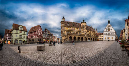ROTHENBURG, GERMANY - OCTOBER 24, 2017: Few unidentified tourists and pedestriants enjoy the blue hour atmosphere on the historic market place