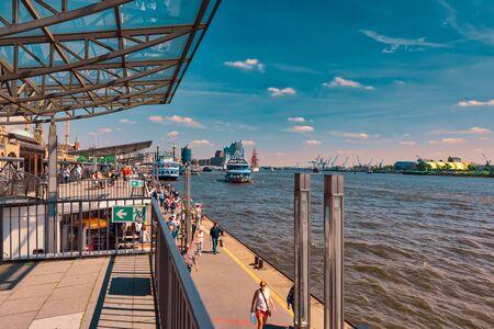 HAMBURG, DEUTSCHLAND - 01. Juni 2019: Touristenspaziergang entlang der Hafenpromenade und versuchen, eines der Touristenboote für die nächste Tour zu erwischen