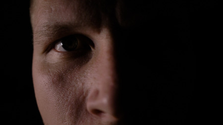 A man looks at the camera in the dark. Close-up eye. Only half of the face is highlighted.