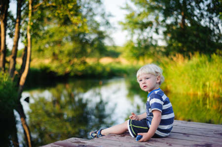 Young boy sitting on the river bridge Stock Photo - 16087988