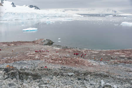Dramatic landscape in Antarctica, penguins and people photo