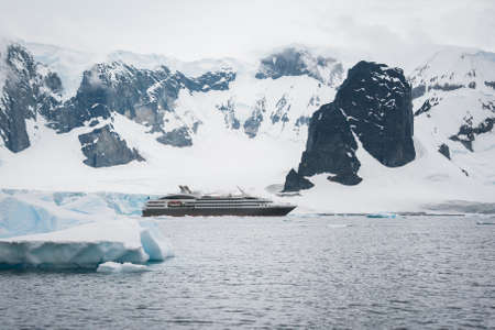 Dramatic seascape in Antarctica, cruise ship in the sea photo