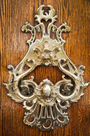 knocker: Old golden metal door handle closeup