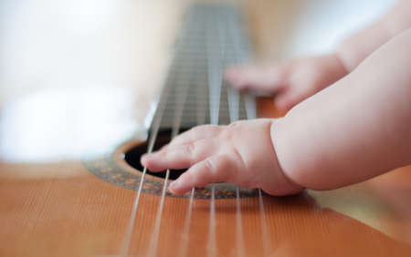 soloist: Baby plaing the guitar Stock Photo