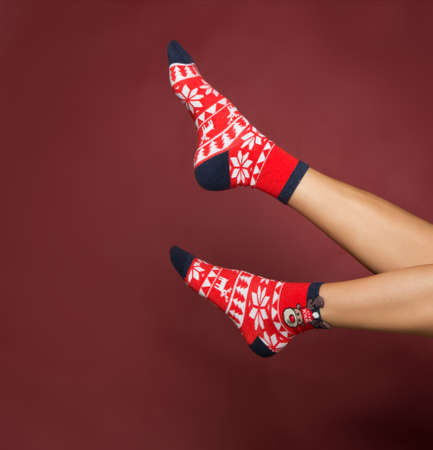 woman legs in color red socks isolated, female legs in Christmas socks