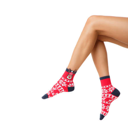 woman legs in color red socks isolated on white, female legs in Christmas socks Фото со стока