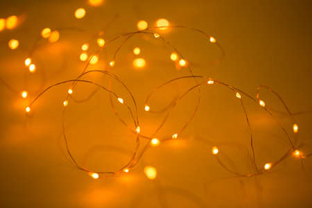 Christmas lights on yellow background with copy space. Decorative garland.