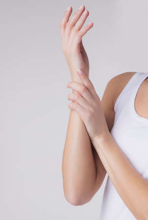 Acute pain in female wrist. Woman massaging her injured hand, closeup